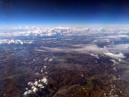 view of earth from an airplane with european mountain landscape with rivers and snow with scattered white clouds and dark blue sky