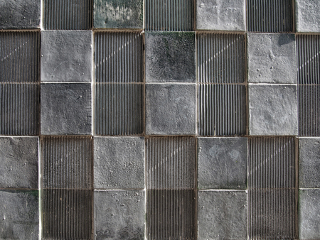 grey concrete wall with geometric square pattern and distressed textures Stock Photo