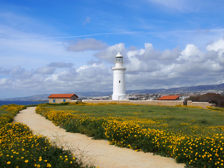 the old lighthouse in paphos cyprus surrounded by historic buildings with spring flowers growing alongside a path leading to the sea with blue sky and white clouds Stock Photo