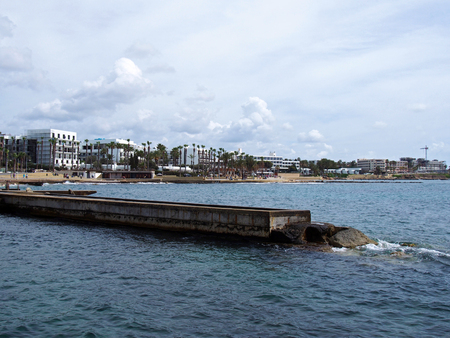 view of the the seafront and harbour in paphos cyprus with hotel buildings and promenade