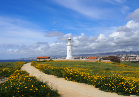 the old lighthouse in paphos cyprus surrounded by historic buildings with spring flowers growing alongside a path leading to the sea with bright blue sky and white clouds