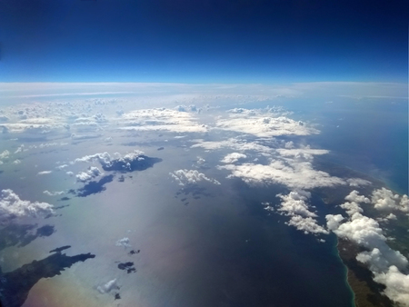 high altitude image of the earth with blue sky and white clouds over the sea with sun reflected on the water and small islands Stock Photo