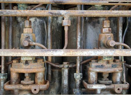 Close up of an old big rusting diesel engine with cylinders and pipes