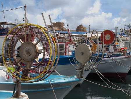 A line of colourful traditional fishing boats moored in paphos harhour in cyprus with blue summer sky and clouds