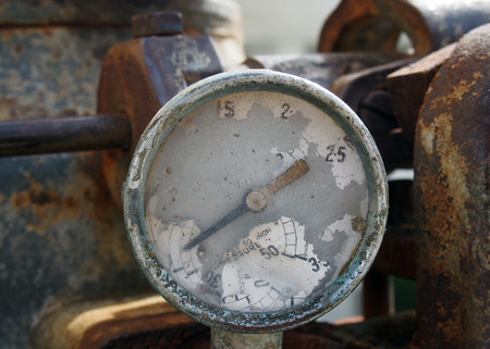 Old broken gauge with traces of numbers on the dial on a large old rusty engine