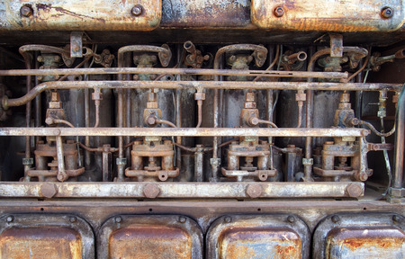 Close up of an old big rusting diesel combustion engine with cylinders rods and pipes