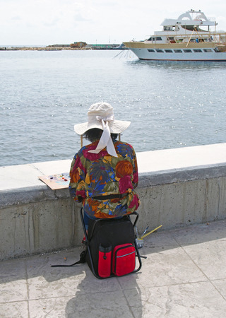 PAPHOS, CYPRUS - March 15, 2018: An older woman paintinga picture in Paphos Harbour Cyprus with a tourist boat setting of to sea