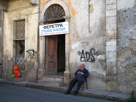 NICOSIA, CYPRUS - March 17, 2018: A coffin maker resting outside his workshop in an old crumbling building in the old town of Nicosia cyprus. The text on the sign reads - Coffins Steleos Kaeitoy phone nimber, house. Editoriali