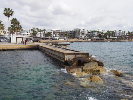 the seafront in paphos cyprus with apartments and white hotel buildings along the promenade with palm trees and jetty