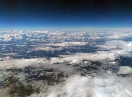 aerial view of the earth from high altitude with dark blue sky and different types of white clouds with snow on a hilly landscape below