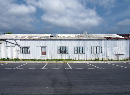 a row of dilapidated abandoned white tin sheet corrugated buildings with empty car park and blue sky and clouds