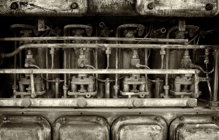 monochrome image of a big old old rusting petrol engine with details of pipes bolts and cylinders