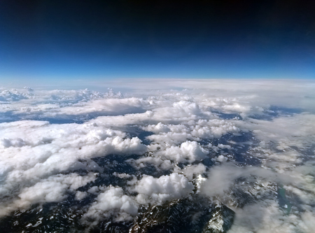 high altitude photograph of the snow covered alps with dark sky and white clouds covering the earth with curved horizon Stock Photo