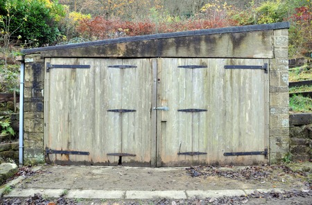 small old stone storage or garage building with decaying wooden doors and rusted hinges with damp walls and roof in a rural setting