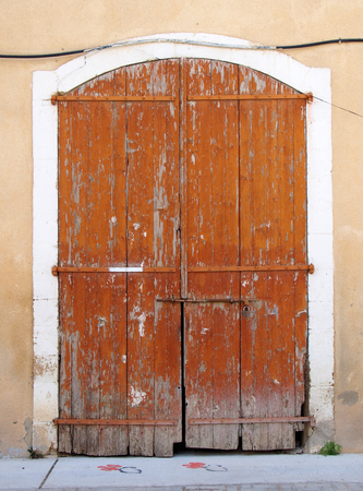 old picturesque decaying brown painted wooden double doors bolted shut with a padlock set in a white stone frame in a faded pink concrete wall on a street Stock Photo