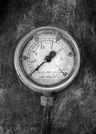 monochrome image of an round industrial pressure gauge with numbers round the dial mounted on a metal surface of a large abandoned diesel powered generator