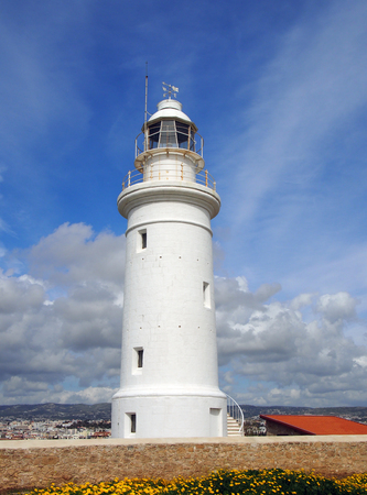 the famous historic white lighthouse in Paphos Cyprus with bright blue sky and beautiful clouds Stock Photo