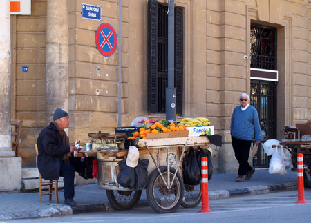 NICOSIA, CYPRUS - March 17, 2018: A Man selling fruit from a stall on a cart sits on the pavement in Nicosia Cyprus on a street corner as a man walks past