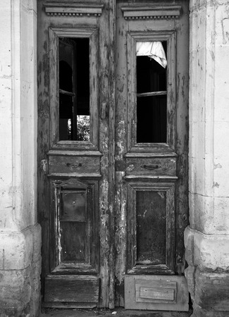 monochrome image of a broken old double door in an abandoned derelict house with broken windows and faded peeling paint in a stone frame Stock Photo