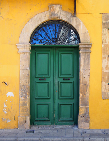 old double green door in a stone frame in a yellow painted wall typical of the style of old buildings in cyprus