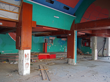 the interior of a derelict abandoned discotheque or nightclub with rubble covered floor and wired hanging from many coloured painted walls and a rubbish covered stage