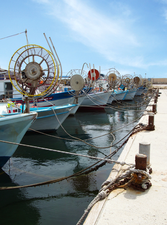 traditional greek fishing boats with spools for lines moored in Paphos harbour in cyprus Stock Photo