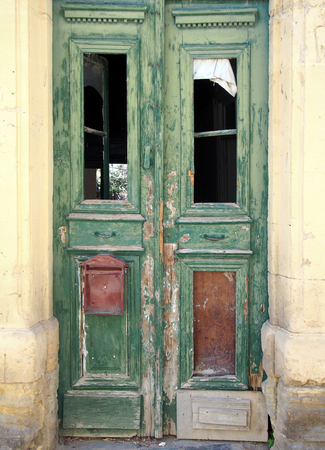 broken old double green doors in an abandoned derelict house with broken windows and faded peeling paint in a yellow stone frame Stock Photo