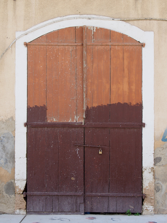 old picturesque decaying half brown painted wooden double doors bolted shut with a padlock set in a white stone frame in a faded pink concrete wall on a street Stock Photo