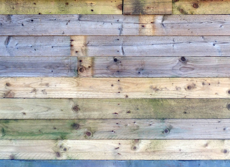 colorful old rustic wooden plank wall or floor with some of the boards stained blue made of patched reused timber