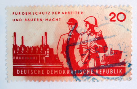 Leeds, England - April 18 2018: An old red east german postage stamp with postal soldiers guarding a factory and a worker Editorial