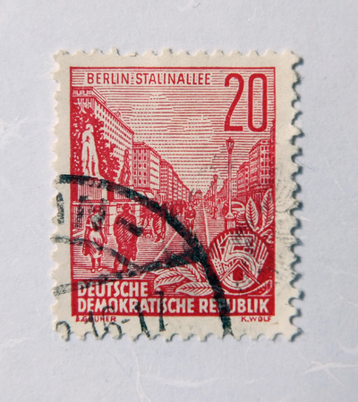 Leeds, England - April 18 2018: An old east german red postage stamp with a street scene commemorating a road called stalinallee