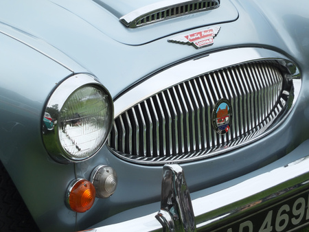 Hebden Bridge, West Yorkshire, England - August 5 2017: Chrome front grill headlamp and bumper of a blue Austin Healey 3000 Sports car at the Annual Hebden Bridge Vintage Weekend Vehicle Show Redakční