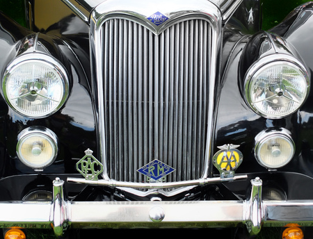 Hebden Bridge, West Yorkshire, England - August 5 2017: Front detail of a black vintage riley motorcar with bumper headlights radiator and badges at Hebden Bridge annual vintage weekend