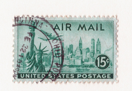 Leeds, England: An old green vintage american air mail postage stamp with the statue of liberty Manhattan and an aircraft