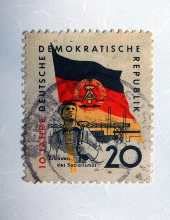 Leeds, England: An old east german postage stamp with an image of a steel worker against the flag of the gdr Standard-Bild - 100374702