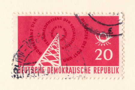 Leeds, England - May 10 2018: An old red est german stamp with an image of a radio transmitter
