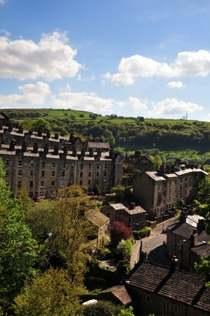 A view of the winding streets and tall stone houses in hebden bridge se in the surrounding west yorkshire countryside with pennine hills and bright summer trees with blue cloudy sky