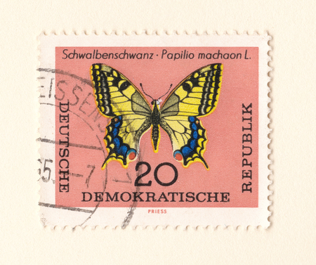 Leeds, England - May 10 2018: An old brown east German stamp with an image of a swallowtail butterfly