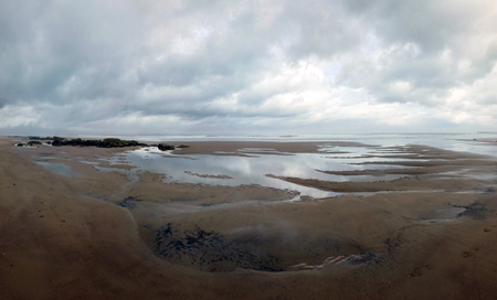 Panoramic view of the beach at sandsend near whitby at low tide with a dramatic stormy cloudy sky reflected in pools of water on the sand with waves on the distant horizon Stock Photo