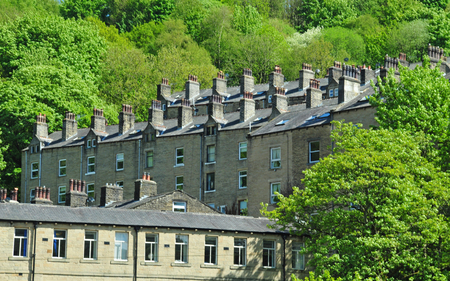 Hillside streets of tall stone houses set in the woodland landscape in Hebden bridge west Yorkshire Stock Photo
