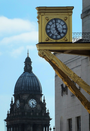 The golden clock on Leeds civic hall with the dome of the town hall in the background