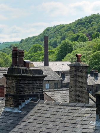 Chimneys and roofs of traditional stone build houses and mills typical of west Yorkshire small towns and villages set against steep valley woodland with blue summer sky