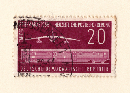 Leeds, England - May 10 2018: An old red east german stamp with an image of a jet bomber and railway train carriage