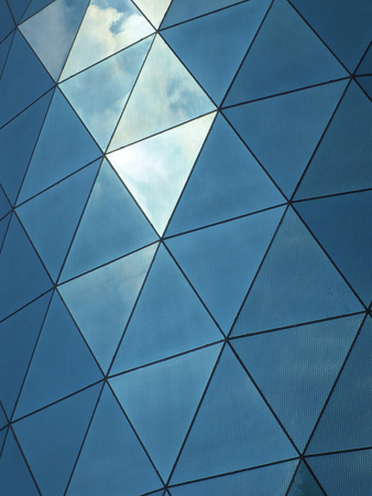 Modern corporate building with angular patterned mirrored windows panes reflecting the sky and clouds