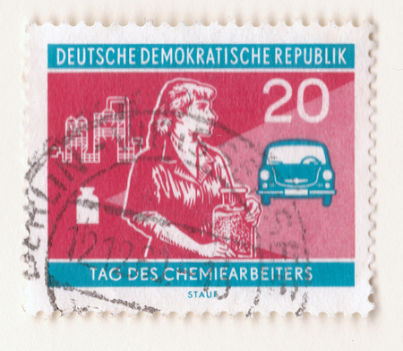 Leeds, England - May 10 2018: An old red east german stamp with an image of a woman chemist holding a jar with an automobile and industrial factory in the background Editorial