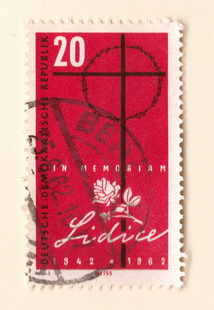 Leeds, England - May 18 2018: An old red east German stamp commemorating the massacre at Lidice with a cross and white rose