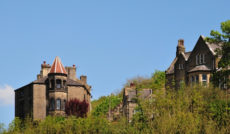 Tall stone gothic houses set in the woodland landscape in Hebden bridge west Yorkshire with blue sky