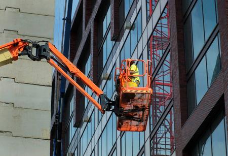 Construction worker on an orange elevated platform on a large modern building site