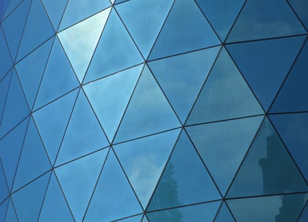 Angular patterned mirrored windows panes reflecting the sky and clouds