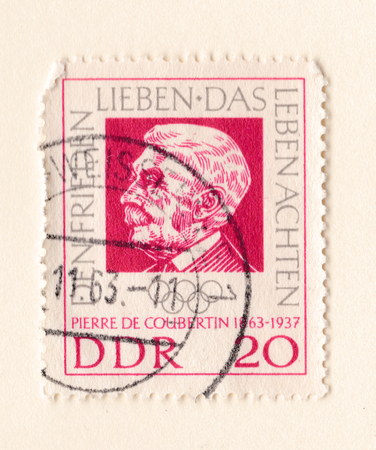 Leeds, England - May 19 2018: An old red east German stamp with an image of Baron Pierre de Coubertin founder of the International Olympic Committee